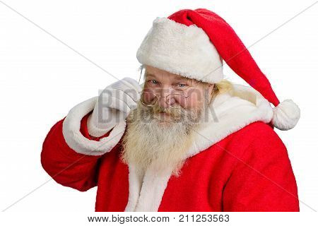 Santa Claus removing his glasses. Portrait of cheerful Santa Claus isolated on white background close up. Santa Clause tuching his eye glasses.