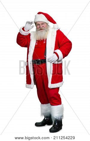 Full length of senior Santa Claus. Happy bearded man in Santa Claus costume standing on white background. Studio shot of Santa Claus.
