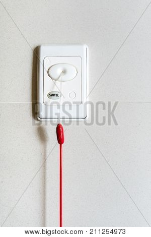 Nurse Call Switch With Emergency Pull Cord Isolated On White Wall In Patient Room.