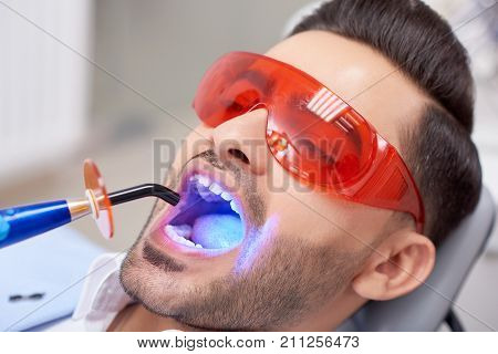 Close up portrait of a handsome young man wearing protective eyewear getting teeth filling done at the dental clinic professionalism safety healthcare medicine smile treatment dentistry.
