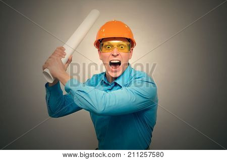 An angry worker engineer swears and yells at someone and waves his project drawings in his hands. crazy architect. Bad job.