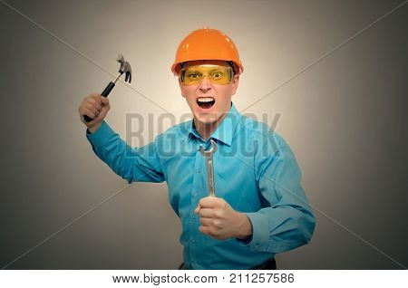 An angry engineer worker with hummer and wrench in his hand yells and screams at someone. Crazy factory worker in rage.
