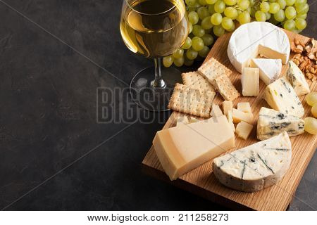 Assorted Cheeses With White Grapes, Walnuts, Crackers And White Wine On A Wooden Board. Food For A R