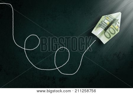 hundred euro paper plane going towards a light beam abstract money concept