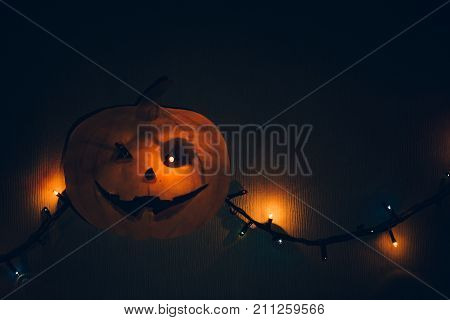 A paper pumpkin with a flashing garland in place of the eyes hanging on the wall. A horrible template for Halloween.