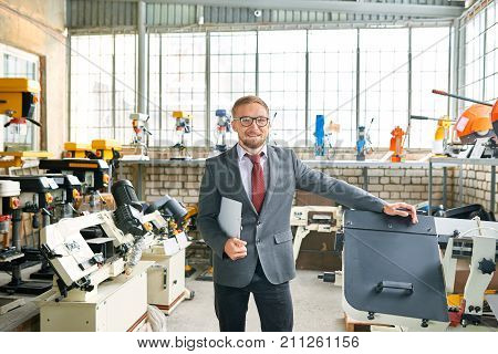Portrait of successful shop assistant wearing suit posing looking at camera, standing by machine tools in industrial  showroom