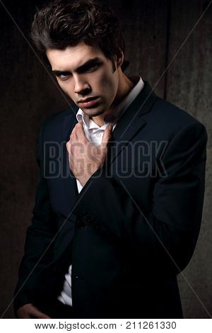 Sexy Serious Handsome Male Model Posing In Blue Fashion Suit And White Style Shirt On Dark Shadow Ba