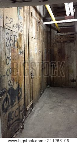 Destroyed basement. Wooden door to the basement closed to a padlock. Painted and destroyed with inscriptions.