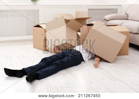 Man crushed underneath cardboard boxes he was carrying. Heavy shopping, burden concept