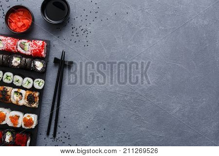 Top view on sushi set at gray background with scattered black sesame. Slate platter with rolls, ginger and soy sauce, chopsicks on rustic surface. Japanese restaurant food and delivery, copy space