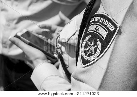 TEL AVIV, ISRAEL. April 9, 2014. Israeli female police officer with an emblem on her uniform holding cellular phone in her hands. Israel police stock image.