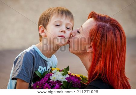 Beautiful Caucasian mother kissing her cute baby boy who gave her a flower bouquet.