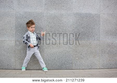Fashion baby boy in gray wear and mint sneakers posing on a gray wall background. Trendy boy standing on the street.