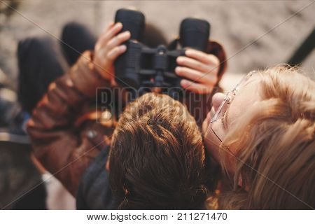 Little caucasian boy watching looking searching for gazing by binoculars with mother top view