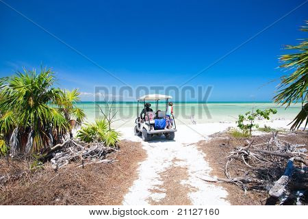 Family driving in golf cart along the tropical beach