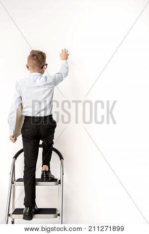 Reaching goal concept. Full length back view of little boy is climbing the career ladder in adult shoes and holding documents while rising hand up. Copy space in the right side. Isolated background