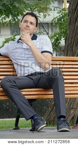 Unshaven Male Wondering Sitting on a Park Bench