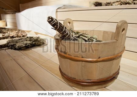 The basin with birch broom close up is on the shelf in the steam room in the bathhouse