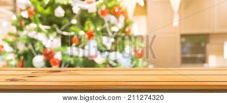 Wooden board empty table top blurred background. Perspective brown wooden table over blur christmas tree background. Panoramic banner. Can be used mock up for montage products display or design layout