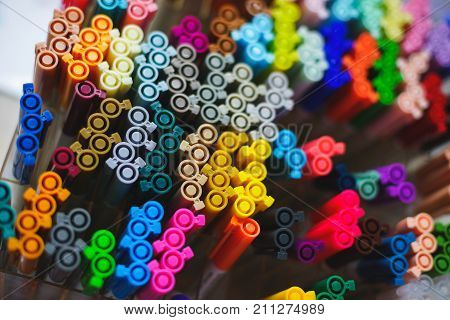 Set of several liners, markers and colored markers of different colors, the top view of the covers. Abstract background from multi-colored caps for plastic pens