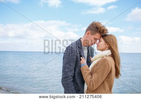 Happy couple in love hugging. Pretty girl and attractive man with a black glasses smiling and laughing outdoors. River on the background. Close-up of couple.