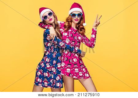 Christmas New Year. Young Woman in Santa Claus hat Smiling. Having Fun Happy. Fashion Sunglasses. Pretty Sisters Best Friends. Twins in Stylish fashion Red Xmas Holiday Dress. Christmas Colorful