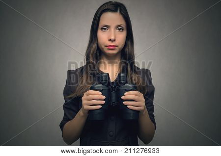 Young sceptical woman holding in hands binoculars in front of her. Find and search.