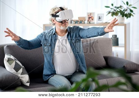 Portrait of joyful senior man using modern technology for entertainment. He is sitting on couch and wearing virtual reality headset. Man is stretching arms forward and smiling