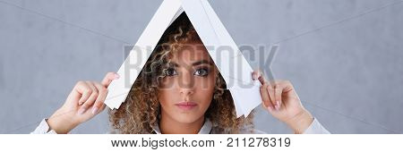 Beautiful woman portrait. Holds paper documents with financial statistics fashion style mulatto curly hair with white locks eye view of the camera lot of work