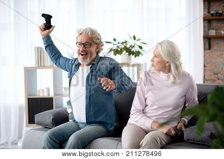 Joyful senior man is celebrating his triumph while winning his wife in console. He is sitting on couch and laughing. Sad woman is looking at him with frustration