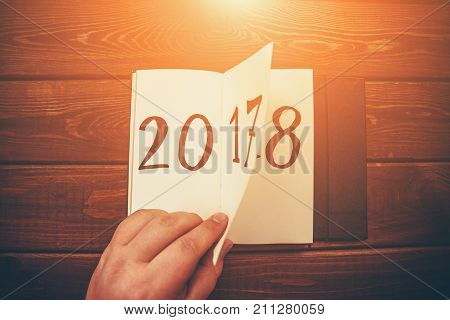 New Year 2018 is coming concept. Hand flips notepad sheet on wooden table. 2017 is turning, 2018 is opening. Top view, retro toned