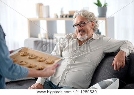 Careful woman is treating her husband by self-baked cookies. Senior man is sitting on couch with relaxation and smiling