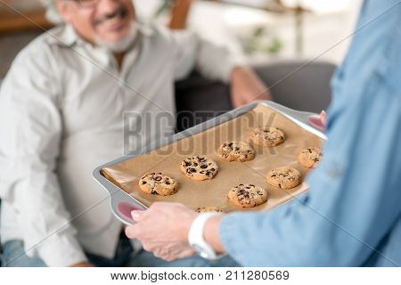 I baked these cookies for you. Close up of female hands holding tray with self-made cookies. Man is sitting on sofa and laughing