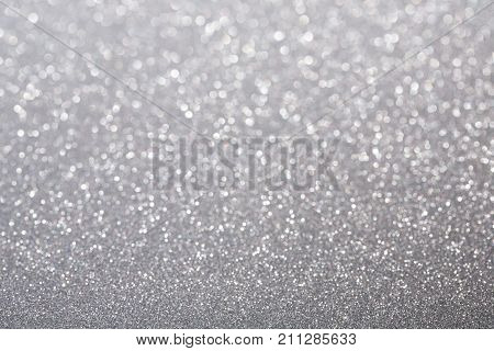 Silver (gray) glitter background. Sparkle texture. Abstract twinkle background blurred for New Years or Christmas holiday