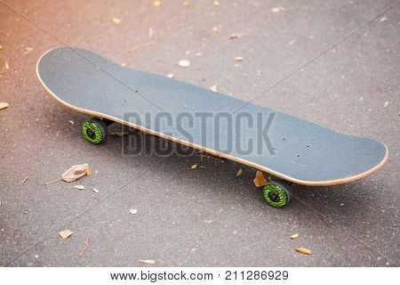 Modern gray skateboard lying on the road. Skate with green wheels for riding. Copy space. Close-up of skateboard. Sport concept.