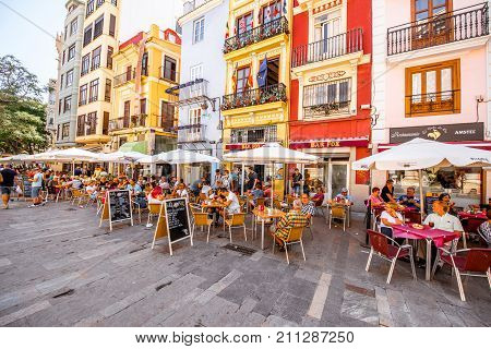 VALENCIA, SPAIN - August 19, 2017: Colorful buildings with cafes and restaurants crowded with tourists near the food market in Valencia city, Spain