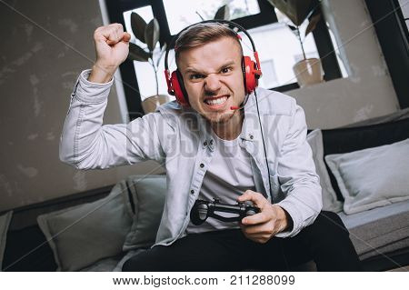Passionate and attractive gamer has won a competition. The game was really hard so young man can't keep his emotions inside of him. He wants to say Yes, I did that and he really did. Close up