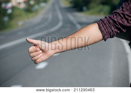 Thumbs up male hand gesture outdoors. Hitchhiker sign on road. Hitchhiking hitching thumbing auto stop concept. Travel trip vacation wanderlust.
