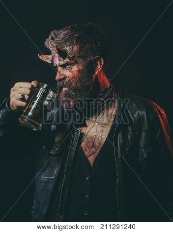 Halloween man demon drink beer on black background. Devil with red blood and wounds on face. Hipster with satan horns hold glass mug. Holiday celebration and party. Bad habits and addiction concept.