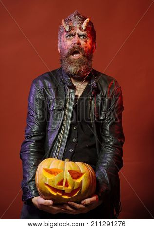 Halloween Man Demon Hold Pumpkin On Brown Background