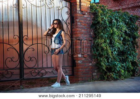 Fashionable young woman in sexy denim shorts and sunglasses. sexy brunette girl with sporty body wearing jeans shorts. stylish, young, brunette hair, denim shorts, sunglasses, be in the city.