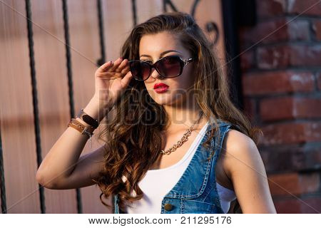 Fashionable young woman in a sexy denim vest and sunglasses. portrait of stylish young brunette woman in sunglasses.
