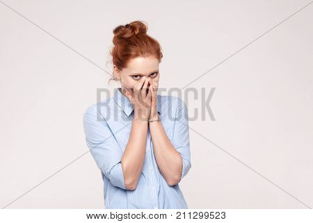 Shame And Liar Concept. Red Haired Woman Covering Mouth With Both Hands Keeping A Secret And Little
