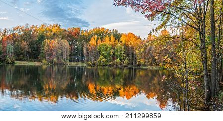 An Autumn panoramic view of Holiday Lake in Manalapan New Jersey.