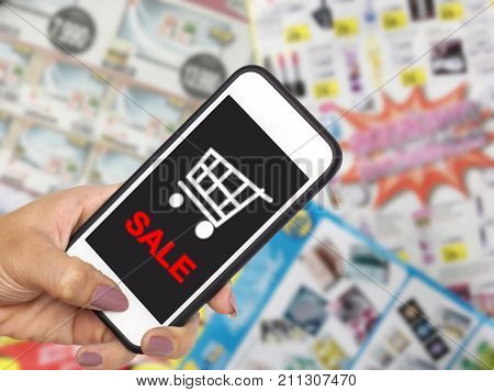 online shopping and e-commerce on internet concept. Hand holding mobile phone with cart symbol on screen display over goods catalogs brochures with promotion blurred background.