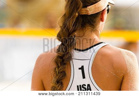 Volleyball beach serving is a female beach volleyball player getting ready to serve the ball.