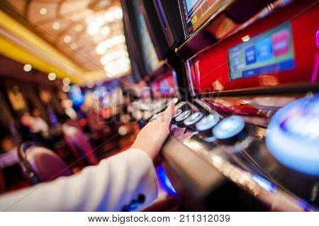 Casino Slot Video Games. Woman Playing Video Slot in the Casino. Hand on Betting Button Closeup Photo. poster