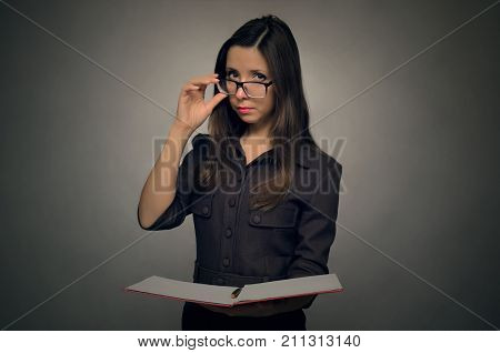 Young serious secretary girl with one hand fixes glasses on her nose and in the other holds a folder with documents. Secretary.High school student.
