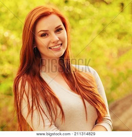 Autumn woman portrait smiling outdoors at the park. redhaired. Toned image with a square ratio