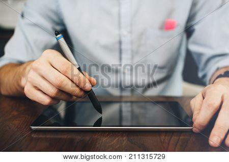 Close Up View Of A Man's Hands And Digital Tablet. Businessman Holds A Stylus In His Hand From Table